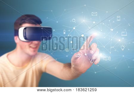 Young impressed man wearing virtual reality goggles with mixed media icons around his finger