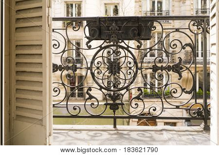 Balcony With Decorative Railing And Shutters In Paris, France