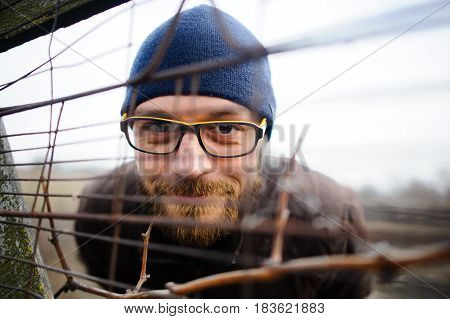 Funny young man with glasses and a beard looks out from behind the fence. He looks through the fence and smiles cunningly.