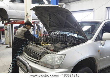 Moscow, Russia - April, 24, 2017: Workers work with a car in a car repair station in Moscow, Russia