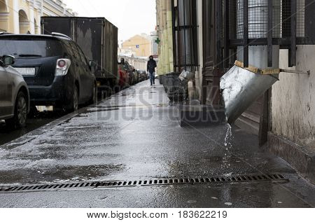 city street man walking on the sidewalk the rain cars parked along the road buildings puddles downpipe spring