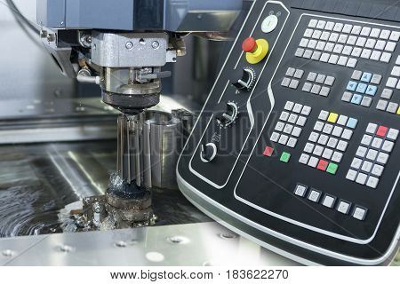 Abstract scene of close-up of the wire - EDM CNC machine while cutting the sample work pieces in light blue tone and controller panel
