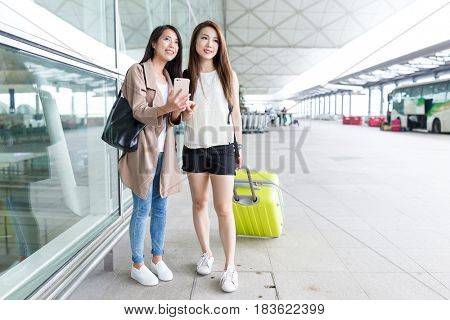 Two women using cellphone and checking the destination in airport