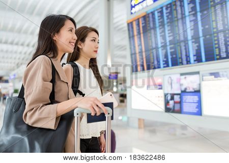 Women checking flight number together in airport