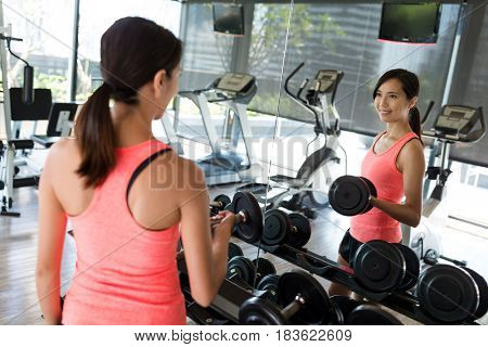 Woman practices weight lifting of the dumbbell in gym