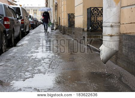 downpipe flowing water pools city streets on the sidewalk there is a person a car parked along the road buildings spring girl with umbrella puddles rain