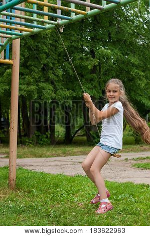 Girl With Posh Long Hair In A White T-shirt And Shorts Swinging On A Simple Swing