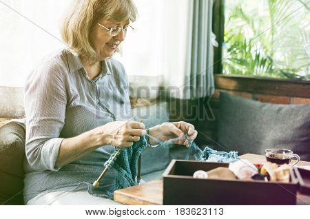 Senior adult woman has knitting activity