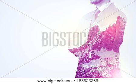 Young businessman in suit standing with sunny snowy mountain and trees graphic.