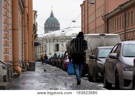 people walking down the street in the rain cars parked along the road buildings the dome of the Kazan Cathedral St. Petersburg puddles spring