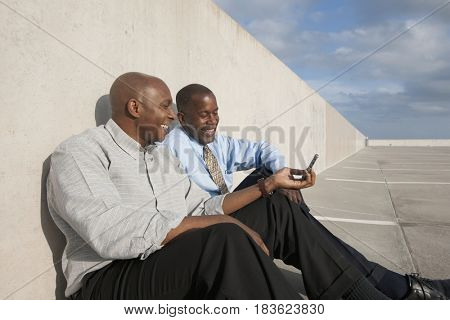 African businessmen looking at cell phone in parking lot