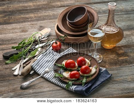 Caprese salad with mozzarella and tomatoes served on pretty rustic plates, antique utensils
