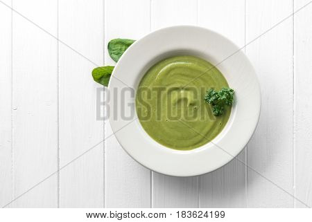 Creamy green spinach soup with some spinach on side, on white wooden table, topview