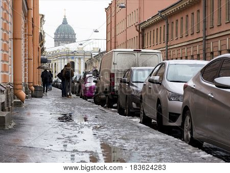 city street Petersburg people walking on sidewalk cars parked along the road buildings drainpipes the dome of the Orthodox Church puddles snow is melting spring