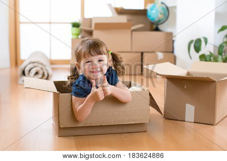 Moving to new apartment. Happy child girl in cardboard box.