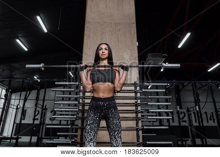 Attractive athletic girl rests after a hard workout in the gym. A sports girl sits and rests after strength training with a barbell.