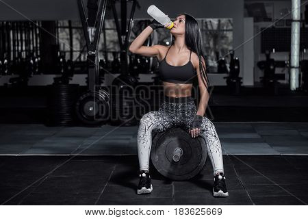 Training in the gym. Fitness girl to to take a breather. Fitness trainer drinks water from a bottle. Fitness Workout