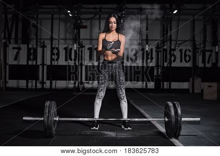 Concept: power strength healthy lifestyle sport. Powerful attractive muscular girl engaged in cross fit training with barbell in the gym. The athlete smeared her hands with talcum powder.