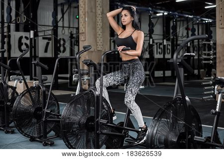 Young attractive woman using exercise bike at the gym. Fitness female using air bike for cardio workout at fitness gym. Woman to burn calories on the air bike.