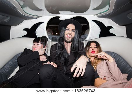 Stylish man and women sitting in a limo and looking at camera. Horizontal indoors shot.