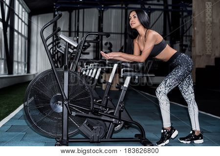 Young attractive woman using exercise bike at the gym. Fitness female using air bike for cardio workout at gym.The girl is resting near a row of bicycles