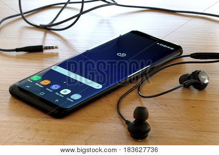 Koszalin, Poland - 27 April, 2017: Black Samsung Galaxy S8 on wooden table. Samsung S8 are new generation smartphone from Samsung. The Samsung S8 is smart phone with multi touch screen
