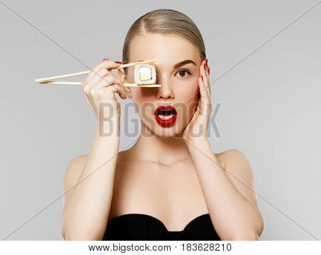 Diet Concept. Nutrition. Beautiful Smiling Woman Eating Sushi Roll With Chopsticks. Fashion Portrait