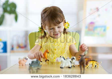 Happy little kid girl. Smiling child toddler plays animal toys at home or kindergarten.