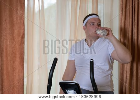 Fat guy exercising on stationary training bicycle and drinking water at home