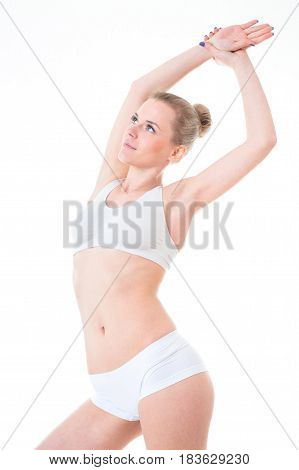 Young woman in white lingerie stretching her arms above her head as she shows off her gorgeous figure isolated on white