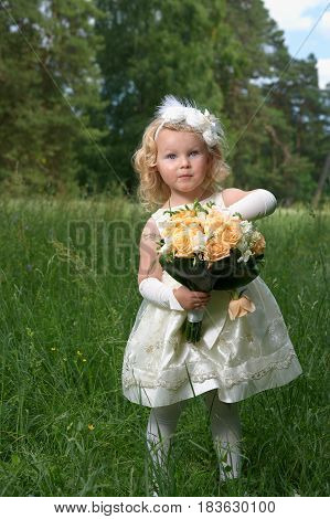 Little princess in a bride dress with a bridal bouquet. Outdoor portrait
