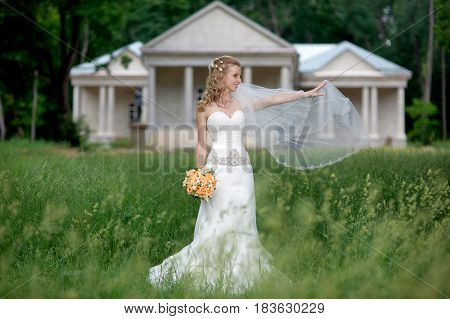 Elegant bride with bouquet in the park