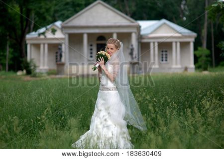 Portrait of Beautiful bride holding wedding bouquet and posing at green Parkland