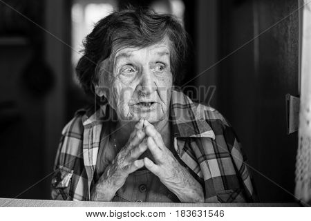 Portrait of excited elderly woman. Black and white photo.