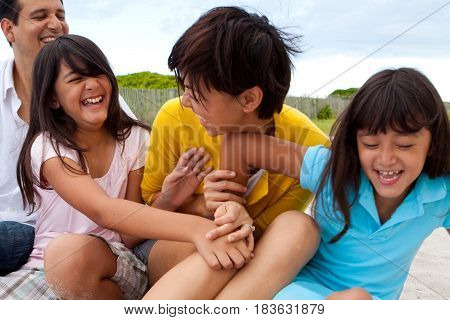 Happy Asian family laughing and playing at the beach.