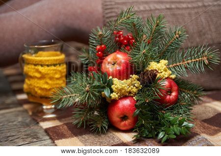 Winter bouquet of fir twigs and Mimosa and ashberry and red apples