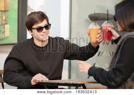 Image of happy young lady sitting outdoors with her brother drinking juice. Looking aside. Focus on man.