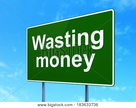 Money concept: Wasting Money on green road highway sign, clear blue sky background, 3D rendering