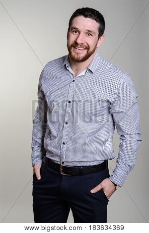 Happy Handsome Smiling Man In Fashionable Shirt Stands On A Gray Background