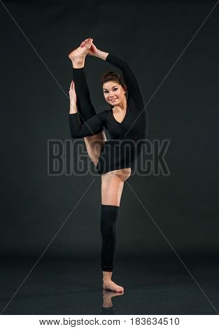 Sporty yoga girl on black background and holds up one feet while stretching