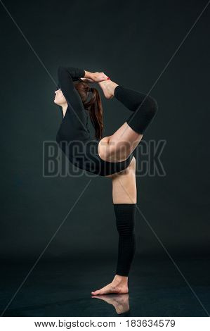 Portrait of healthy young woman doing yoga exercise isolated over black background
