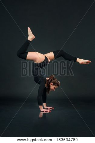 Hand Stand. Girl Acrobat Performer doing Hands Standing Upside Down. Woman Handstand.