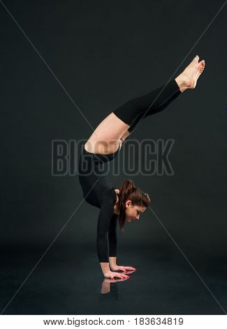 Young woman dancer in black clothing on black background.