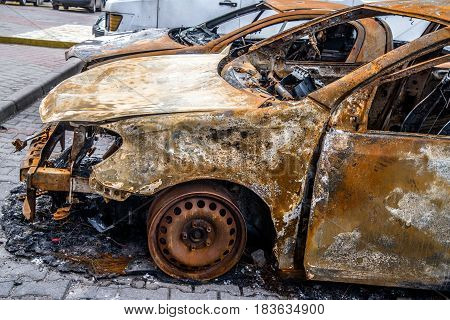 Burnt car is on the asphalt road