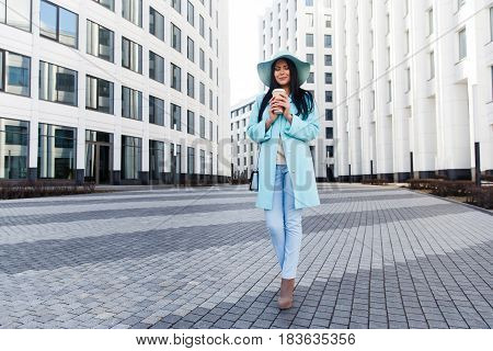 Portrait of beautiful brunette in hat at center of city