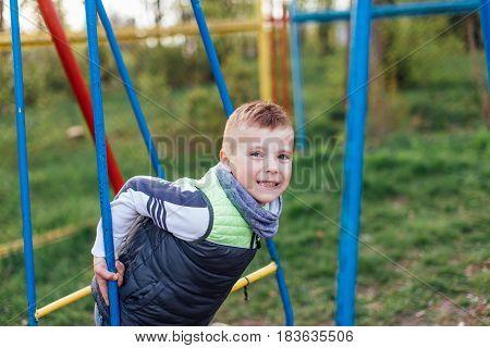Little Boy Play On Playground With Blur Park Background