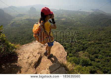 successful woman photographer taking photo on mountain peak cliff