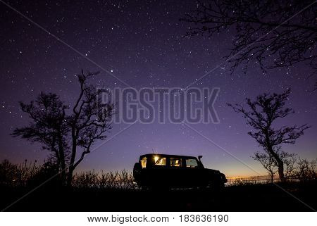 Leningrad region, Russia - April 22, 2017. Jeep Wrangler under the starry sky on the shore of the bay. Wrangler is a compact SUV produced by Chrysler