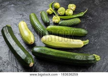 Different Green Fresh Seasonal Vegetables On Black Table Top Background