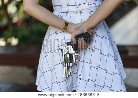 Young pretty Asian woman hiding a hand gun behind her back with both hands.